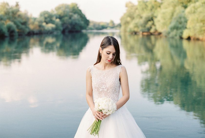 Wedding dresses for Greece showing bride in front of lake
