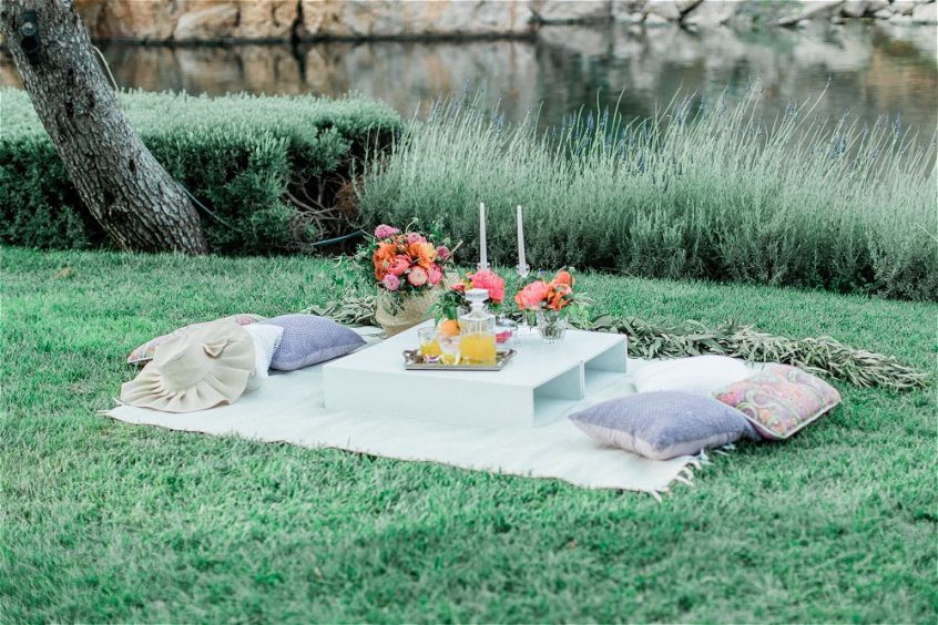 Picninc with pillows, flowers and candles setup for an elopement in Greece