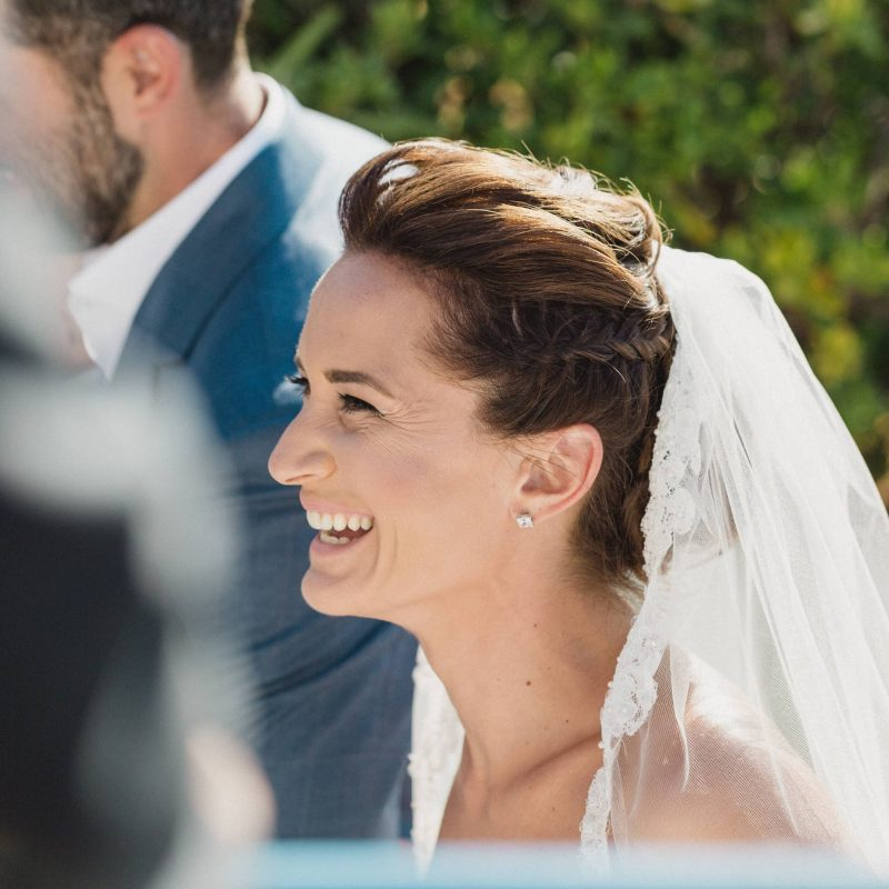 Beautiful bride with veil and braids bridal up-do smiling while she sees her husband to be at our event.