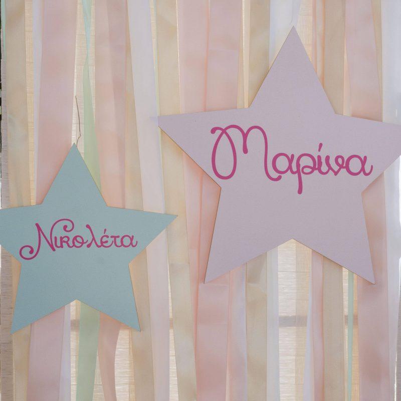 Marina & Nikoleta's baptism details:Paper star decorations on a backdrop with ribbons.