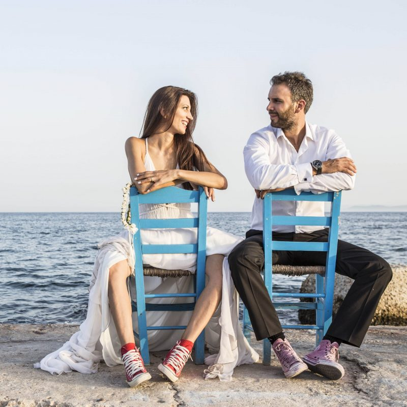 Groom and bride wearing converse all star shoes posing on two blue wooden chairs on The day of our wedding and christening.