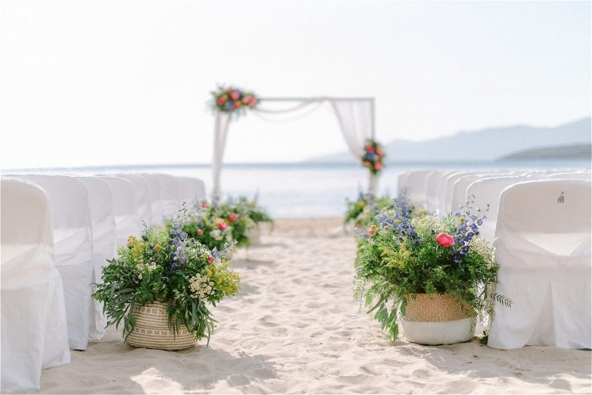 Ceremony on the beach decorated with beautiful flower arrangements